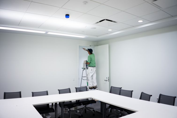 A man puts finishing touches on a doorframe in a meeting room off the cafeteria (Photo: Jake Naughton).
