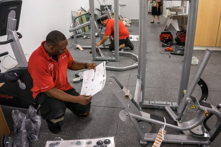 Men assemble workout equipment in the school's new fitness room (Photo: Jake Naughton).