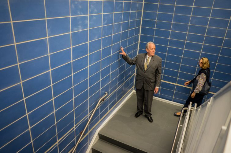 David Kleiser gestures towards the blue walls in the stairwell, part of the school's official colors of blue and gray (Photo: Jake Naughton).