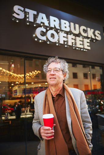 SCG Retail's David Firestein, holding his flat white coffee, hits a Starbucks  in person at least once daily (Photo: Yvonne Albinowski/for Commercial Observer).
