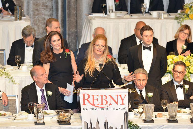 Darcy Stacom of CBRE, center, and sister Tara Stacom of Cushman & Wakefield, left, accepting the Bernard H. Mendik Lifetime Leadership in Real Estate Award.