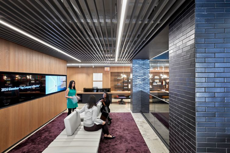 Carpeting and wooden panels on the walls with dark gray bricks are some featured materials in the office's design. Photo: Gensler.