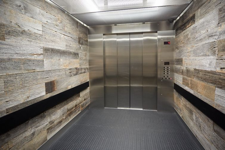 Elevator interiors at the Bruckner Building feature reclaimed wood siding. Photo: Harry Zernike/ for Commercial Observer.