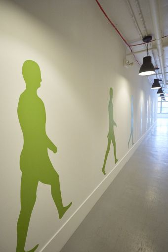 4th floor corridor, which has lime green figures painted on it. Photo: Harry Zernike/ for Commercial Observer.