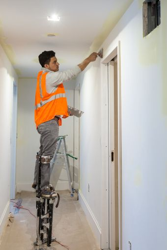 A worker plastering walls in the hallway while standing on stilts. Photo: Melissa Goodwin/For Commercial Observer