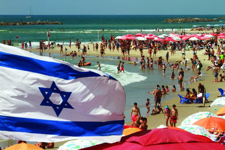 An Israeli flag flutters above umbrellas on the beaches of Tel Aviv. Photo: AFP/GIL COHEN-MAGEN