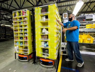 A worker collaborates with a robot carrying a load of goods at an Amazon warehouse.