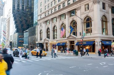 New York, NY, USA - November 4, 2014: the traffic at the 5th Avenue, the most famous shopping street in the world, with multiple luxury brand shops, with the flagship Polo Ralf Lauren store visible on the corner.