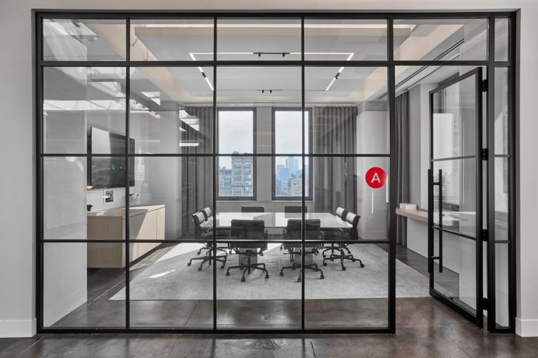Meeting and private rooms at Winton Capital's offices at 315 Park Avenue South have glassed walls with black metal framing in a grid pattern.