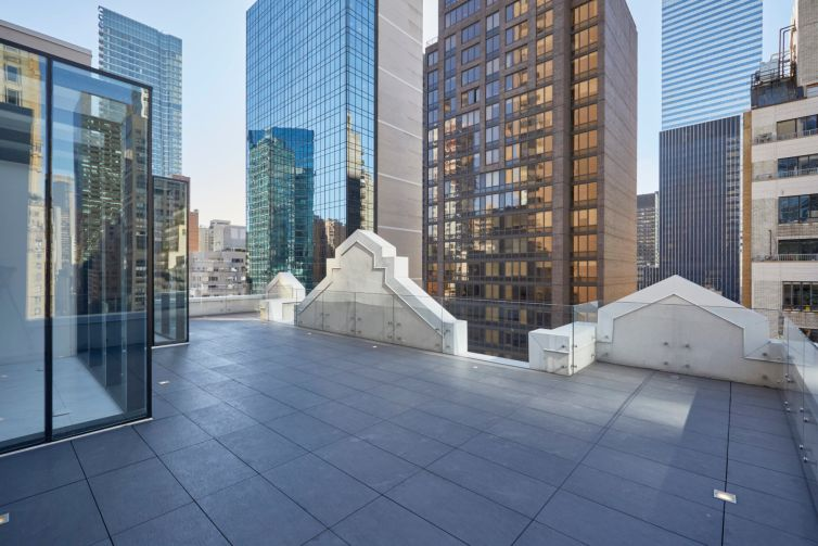 The renovated penthouse has a terrace overlooking Midtown.