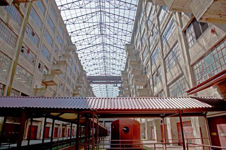 The atrium of Building B at the Brooklyn Army Terminal features an open skylight, dozens of loading docks and a disused train.