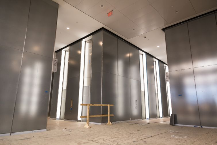 Light reflecting off the woven metal panels that are covered by sheets of glass on the lobby.
