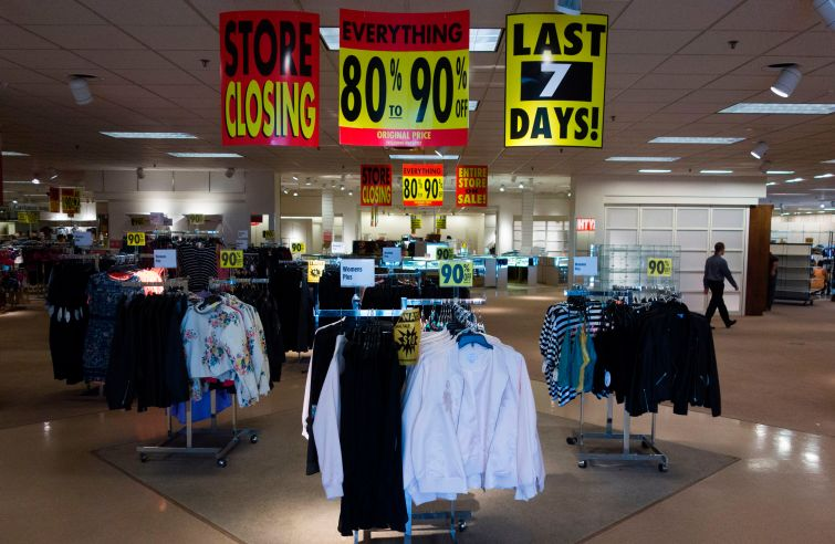 A store with racks of clothing and there are going out of business signs above the racks.