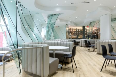 Frank Gehry's glass walls and curved seating originally designed for Condé Nast's cafeteria have been updated to a lighter color palette on the amenity floor at 4 Times Square.