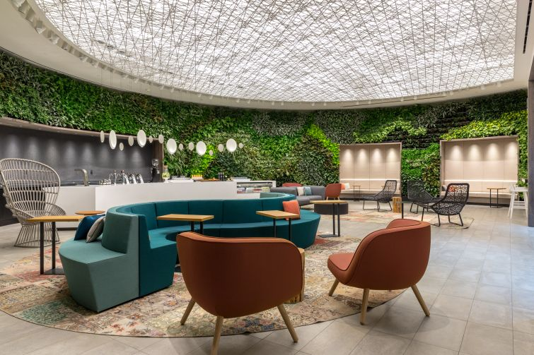 """The Green"" room on the amenity floor at 4 Times Square features a 106-foot long floor to ceiling plant wall, a bar with beer and wine on tap and a variety of seating options for tenants to work at or relax in."