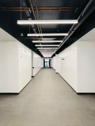 The newly renovated and extended corridor has white tiled walls and porcelain floors.