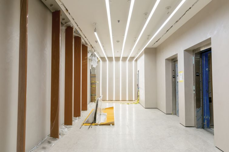 The lobby of the building features LED lighting strips and stone flooring.