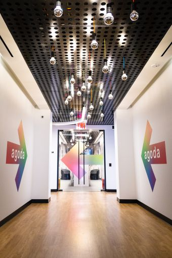 Off the elevators, giant colorful arrows and hanging light bulbs lead guests to Agoda's space. lightbuild