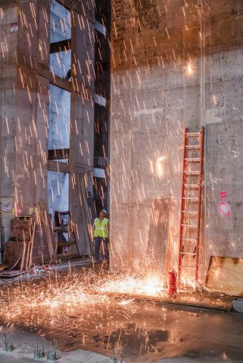 Sparks fly as laborers work on the lobby of the building.