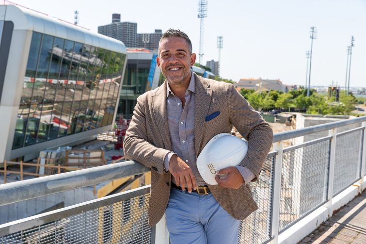 Joseph Ferrara of BFC Partners with his Empire Outlets project behind him.