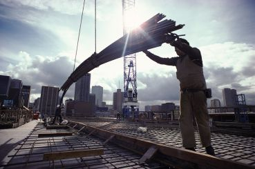 A crane lowers girders down to two workers on a construction site.