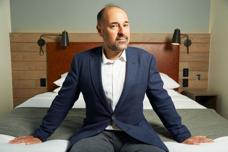 Mark Gordon sits on a bed at the Moxy Downtown, a millennial-focused hotel he recently developed in the Financial District.