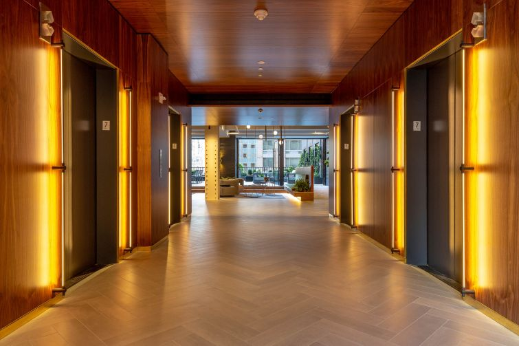 The elevator bank, clad in rich wood and long brushed brass lighting fixtures, opens to the lounge area and terrace.