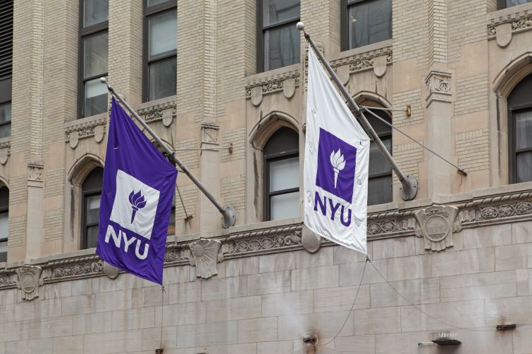 Purple and white NYU flags hang from a New York University building on West 4th Street in Manhattan.