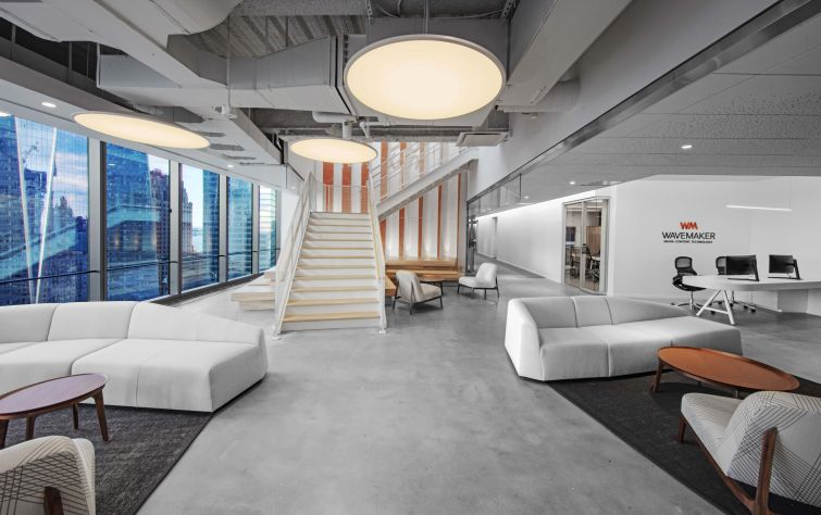 One firm, Wavemaker, has a muted seating area with orange accents and light wood.