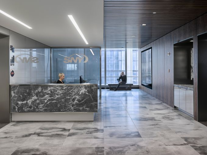 A formal reception area with marble floors for SportsNet contrasts with the rest of its office.