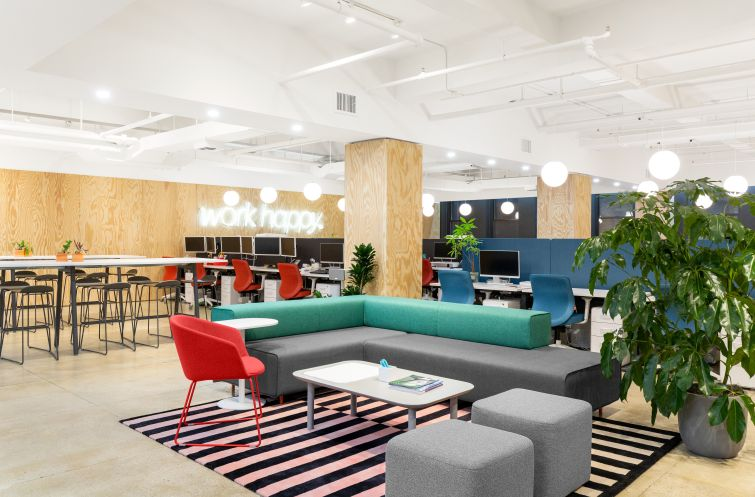 """Poppin redesigned its office to create a homey feel with blonde wood, colorful furniture and a neon version of its """"Work Happy"""" slogan."""