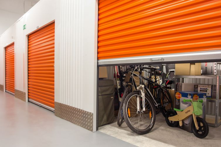 A partially opened large door with stuff just beyond it, including a bike.