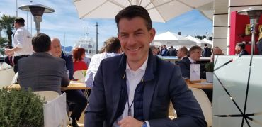 Commerz Real CEO Andreas Muschte at his company's outdoor table in the Frankfurt pavilion at MIPIM.