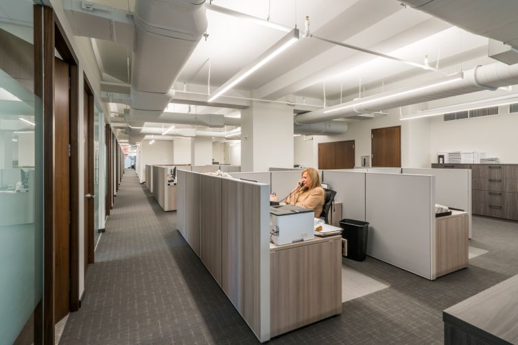 Much of the office is designed in grays, whites and walnut wood.