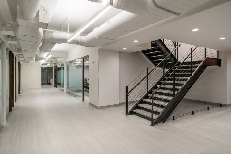 Designer Tamara Eaton tried to carry the industrial vibe of the column into other parts of the office using a black metal staircase.