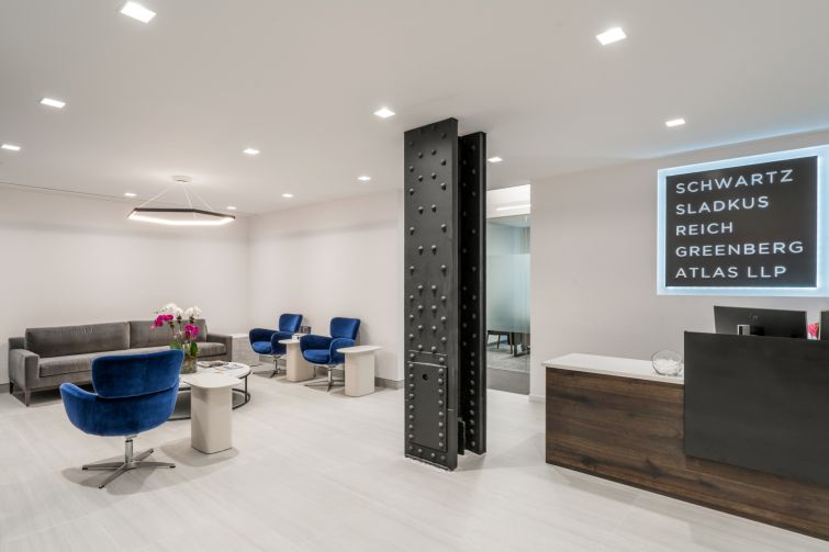 Schwartz Sladkus Reich Greenberg Atlas' new offices at 444 Madison Avenue feature an exposed metal column and blue modernist chairs in the reception area.