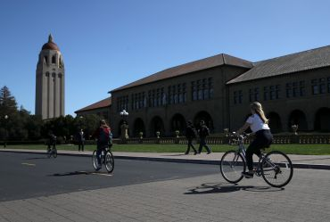 Cyclists ride by Hoover Tower on the Stanford University campus on March 12, 2019 in Stanford, California.