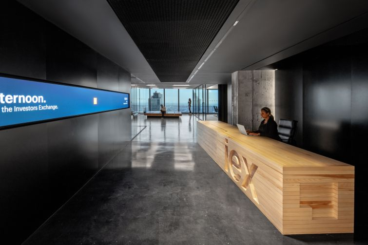 IEX's entryway is dark and features a natural wood reception desk and a long screen that displays market data and news.