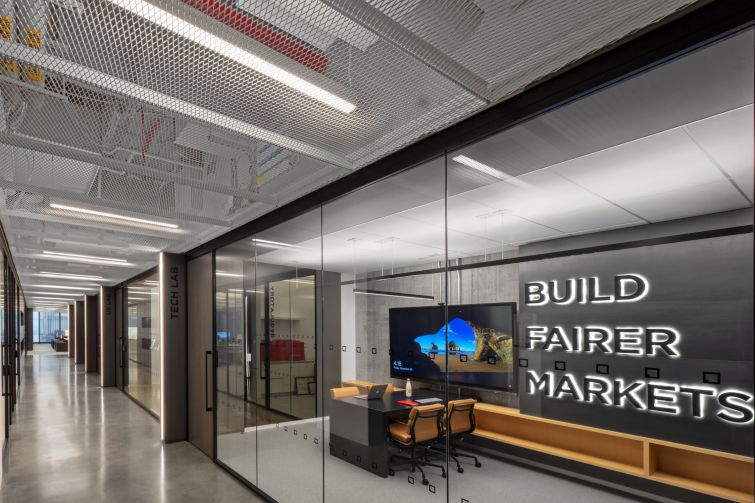 """One conference room is emblazoned with the message """"Build Fairer Markets,"""" the company's motto. It has a high-tech display so the company's programmers can do code reviews there."""