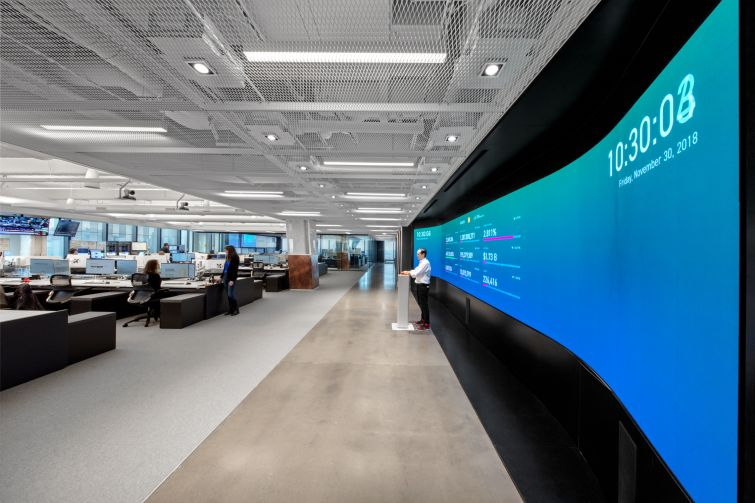 The main work space features a 30-foot-long screen and a pedestal where IEX opens and closes its stock exchange every day.