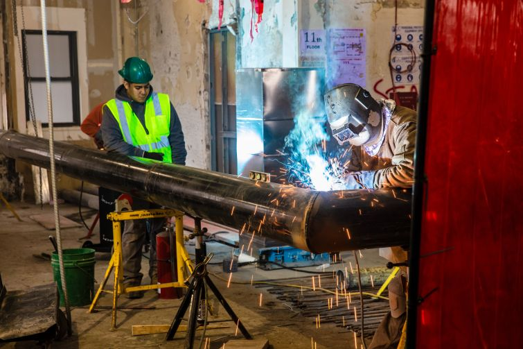 Workers weld new columns to help support the expansion at 150 Fifth.