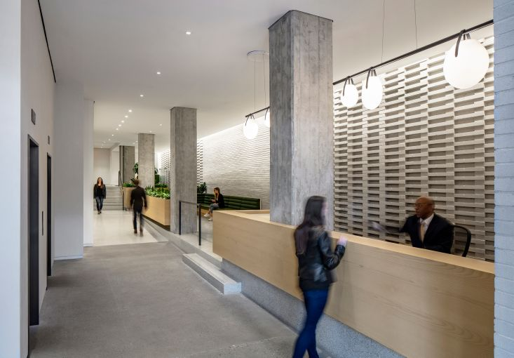 A+I widened the narrow lobby at 155 Avenue of the Americas and added a patterned brick wall to make the space more interesting.