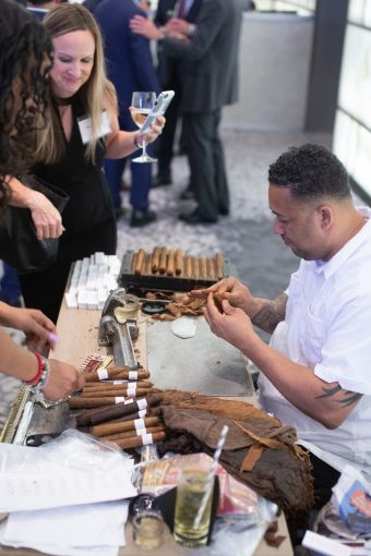 Greystone's Karen Marotta looks on as cigars are rolled at the bar sponsored by Stroock & Stroock & Lavan.