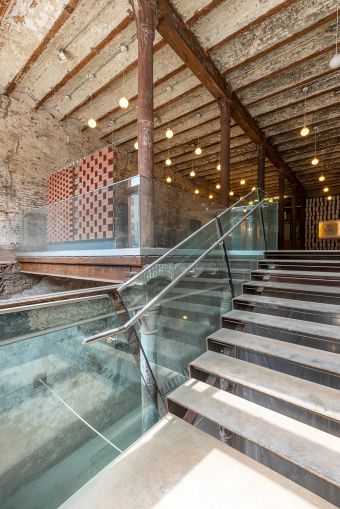 A glass railing and open staircase showcases the Malt Building's historic past while providing a unique entry for a future retail tenant.