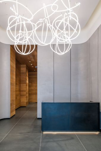 The 18-foot-tall lobby was renovated with wooden and concrete walls and a neon chandelier-sculpture made by Precision Neon.