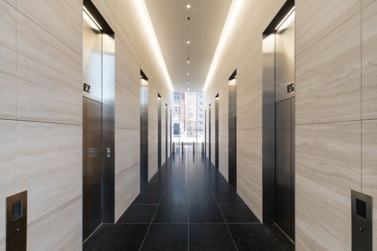 The white marble continues into the elevator lobby, which has bright overhead lighting and stainless steel elevator cabs.