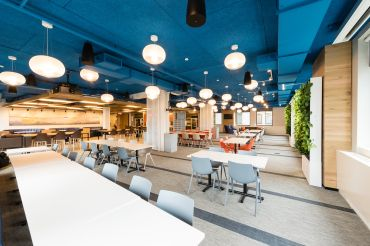 Macmillan's new offices include a full floor of common spaces, including a large cafeteria with plant walls and a variety of seating.