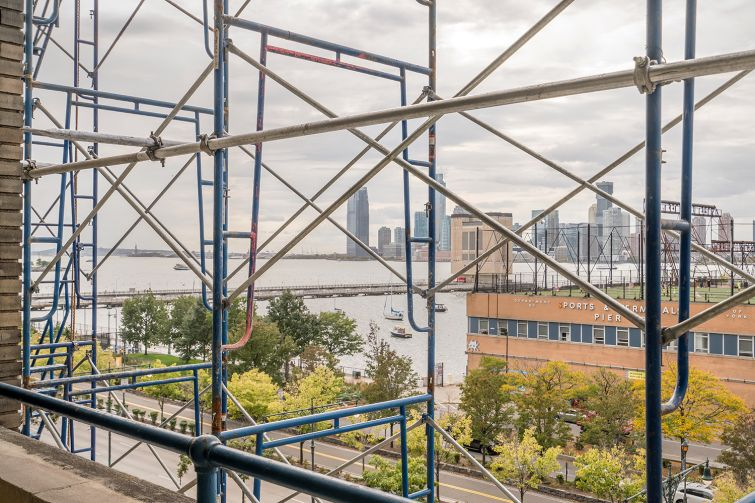 Views through the scaffolding of Pier 40, the Hudson River and New Jersey.