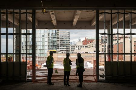 Oxford's Adam Frazier (left) and Kate Bicknell (center) standing on top of the historic railbeds at St. John's Terminal, looking north into Hudson Square and up to Hudson Yards.