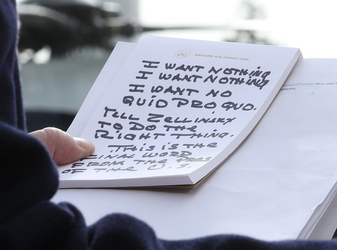 Donald Trump holds handwritten notes outside the White House.